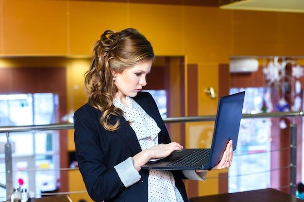 Junges mädchen, das in einem café steht und an laptop arbeitet Premium Fotos