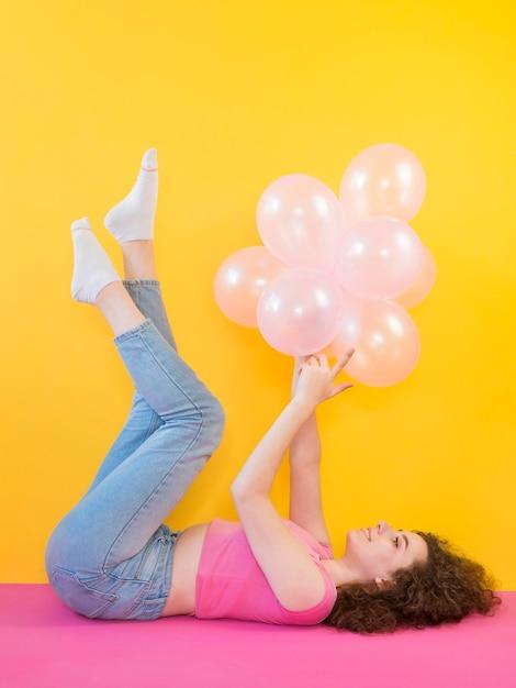 Junges mädchen, das rosa luftballons hält Kostenlose Fotos