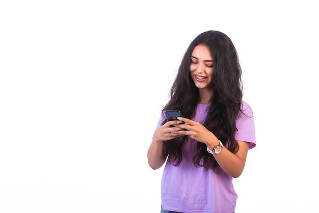 Junges mädchen, das selfie nimmt oder einen videoanruf auf weißem hintergrund macht und positiv aussieht. Kostenlose Fotos
