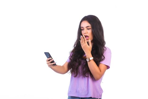 Junges mädchen, das selfie nimmt oder einen videoanruf macht und überrascht wird Kostenlose Fotos