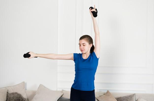 Junges mädchen, das zu hause mit gewichten trainiert Kostenlose Fotos