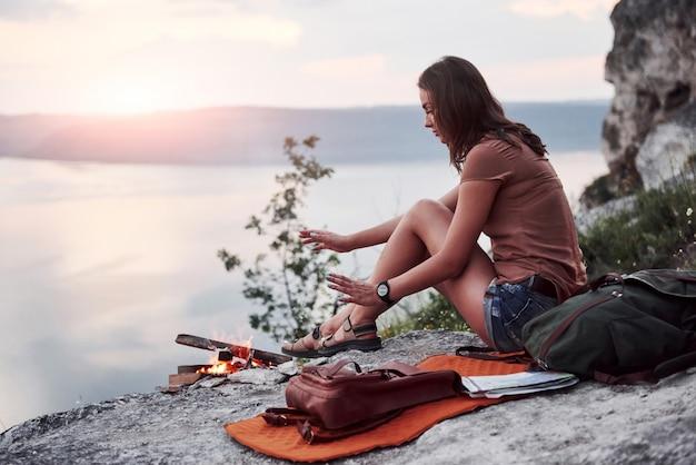 Junges mädchen des hipsters mit rucksack, der sonnenuntergang auf spitze des felsenberges genießt. touristenreisender auf hintergrundansichtsmodell Premium Fotos