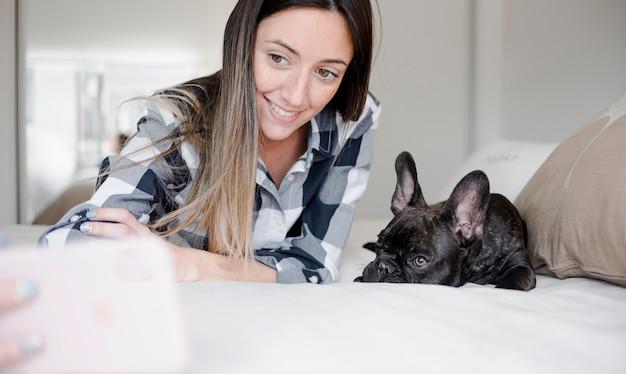 Junges mädchen des smiley, das ein selfie mit ihrem hund nimmt Kostenlose Fotos