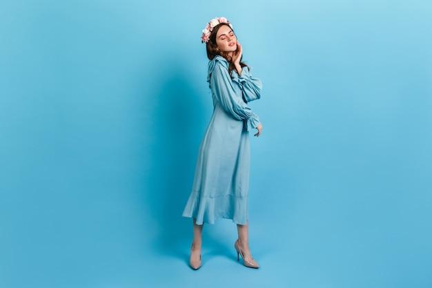 Junges mädchen im langen kleid, das auf blauer wand aufwirft. modell mit rosen im haar berührt sanft das gesicht. Kostenlose Fotos