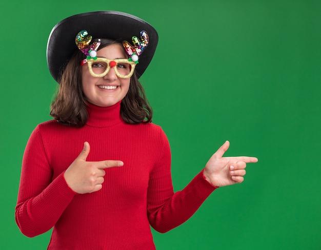 Junges mädchen im roten pullover trägt lustige brille und schwarzen hut, der kamera lächelnd betrachtet Kostenlose Fotos