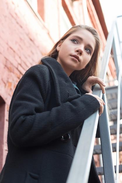 Junges mädchen im schwarzen mantel, der auf treppen mit backsteinmauer auf hintergrund steht. einsamkeit. Premium Fotos