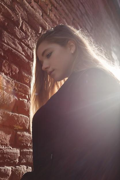 Junges mädchen im schwarzen mantel, der vor einer backsteinmauer in der schönen sonnenunterganghintergrundbeleuchtung steht. einsamkeit Premium Fotos