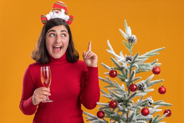 Junges mädchen im weihnachtspullover, der lustiges stirnband hält, das glas champagner glücklich und überrascht neben einem weihnachtsbaum über orange hintergrund hält Kostenlose Fotos