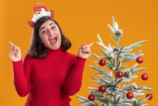 Junges mädchen im weihnachtspullover, der lustiges stirnband trägt, das kamera glücklich und aufgeregt neben einem weihnachtsbaum über orange hintergrund betrachtet Kostenlose Fotos