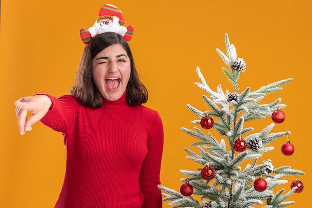 Junges mädchen im weihnachtspullover, der lustiges stirnband trägt, das neben einem weihnachtsbaum über orange hintergrund schreit Kostenlose Fotos