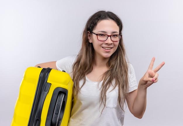 Junges mädchen im weißen t-shirt, das reisekoffer hält, der fröhlich siegzeichen oder zwei nummer zeigt Kostenlose Fotos