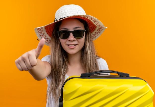 Junges mädchen im weißen t-shirt im sommerhut, der reisekoffer lächelnd zeigt daumen hoch Kostenlose Fotos