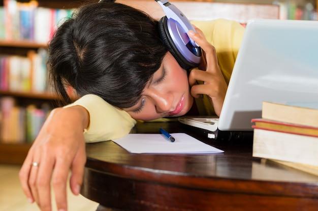 Junges mädchen in der bibliothek mit laptop und kopfhörern Premium Fotos