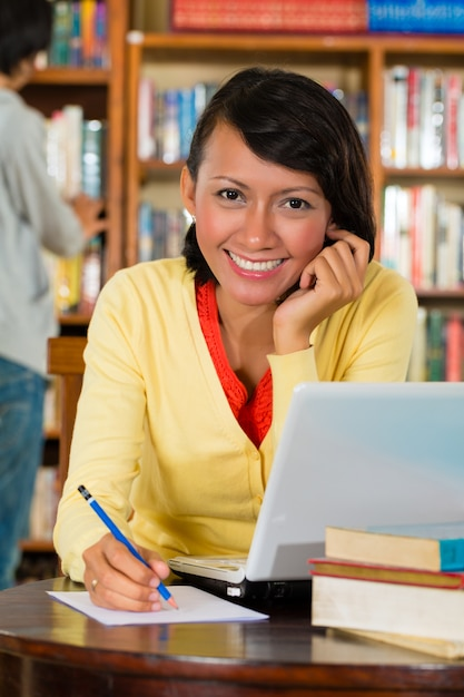 Junges mädchen in der bibliothek mit laptop Premium Fotos