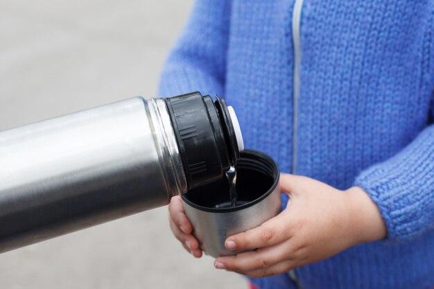 Junges mädchen in einem blauen strickpullover trinkt tee oder kaffee von einer thermoskanne tasse im freien. Premium Fotos