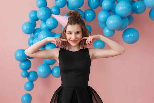 Junges mädchen in einem geburtstagshut, der finger auf wangen an der rosa wand und den blauen ballonen halten aufwirft Kostenlose Fotos