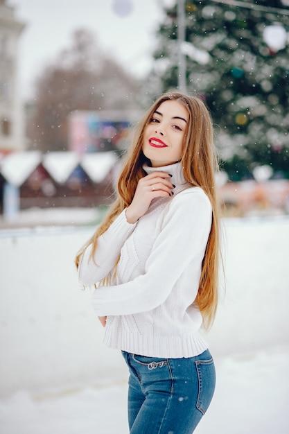 Junges mädchen in einer weißen strickjacke, die in einem winterpark steht Kostenlose Fotos