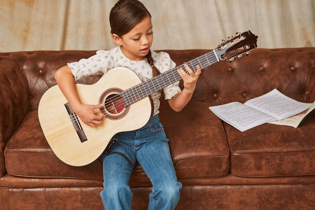 Junges mädchen lernt, wie man zu hause gitarre spielt Kostenlose Fotos
