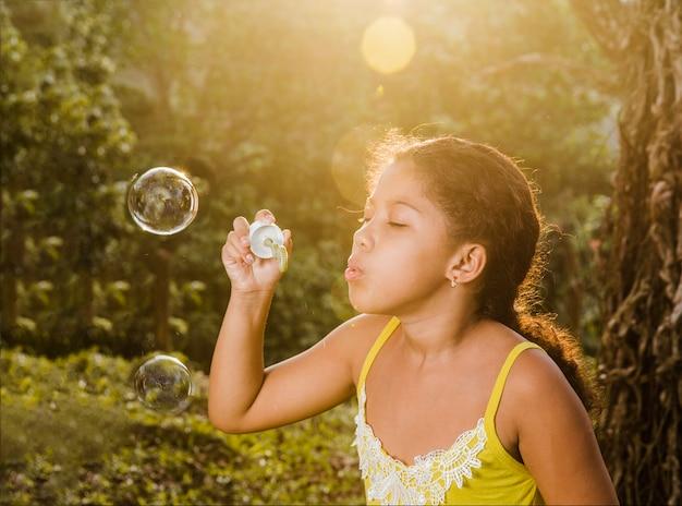 Junges mädchen macht eine seifenblase Kostenlose Fotos