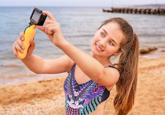 Junges mädchen macht selfie und video am strand. Premium Fotos
