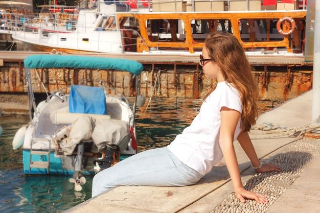 Junges mädchen mit dem langen haar sitzt auf dem pier im yachthafen und betrachtet das blaue meer Premium Fotos