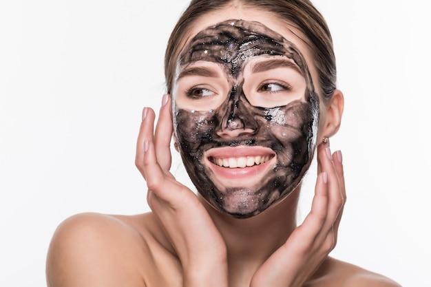 Junges mädchen mit einer schwarzen kosmetischen maske auf ihrem gesicht, die einen pinsel lokalisiert auf einer weißen wand hält Kostenlose Fotos