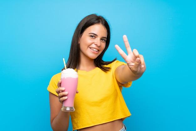 Junges mädchen mit erdbeermilchshake über lokalisierter wand lächelnd und siegeszeichen zeigend Premium Fotos