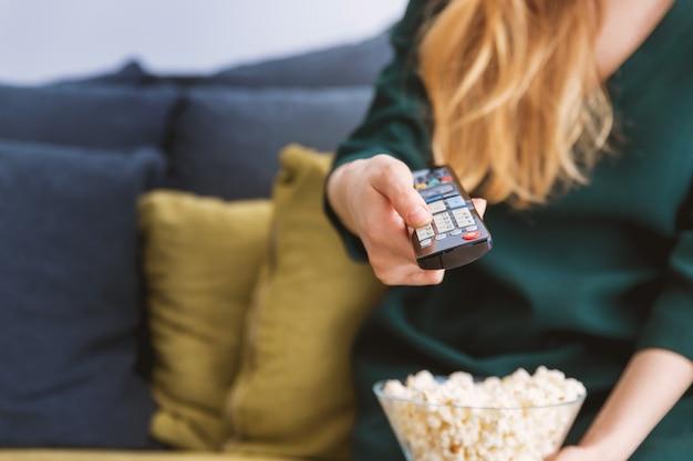 Junges mädchen mit fernsehdirektübertragung und einem popcorn zu hause Premium Fotos
