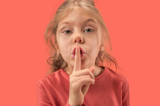Junges mädchen mit ihrem finger auf ihrem mund auf korallenwand Kostenlose Fotos