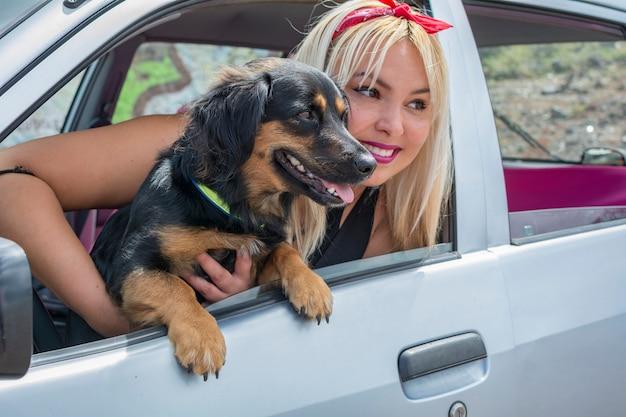 Junges mädchen mit ihrem hund im auto, das auf sommerferien reist. Premium Fotos