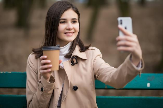 Junges mädchen mit kaffeetasse macht selfie im herbstpark Kostenlose Fotos