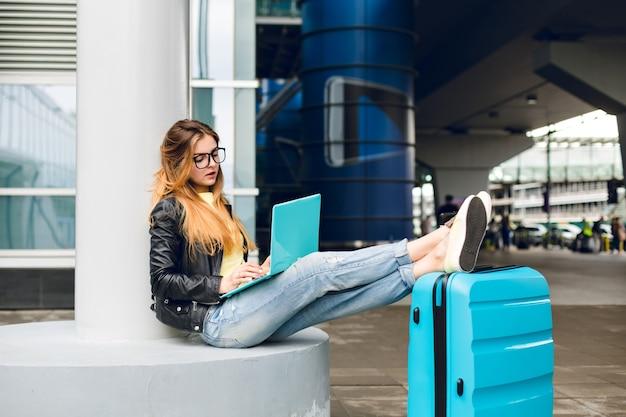 Junges mädchen mit langen haaren in der schwarzen brille sitzt draußen im flughafen. sie trägt jeans, schwarze jacke und gelbe schuhe. sie legte ihre beine auf einen koffer in der nähe. sie langweilt sich beim tippen auf einem laptop. Kostenlose Fotos