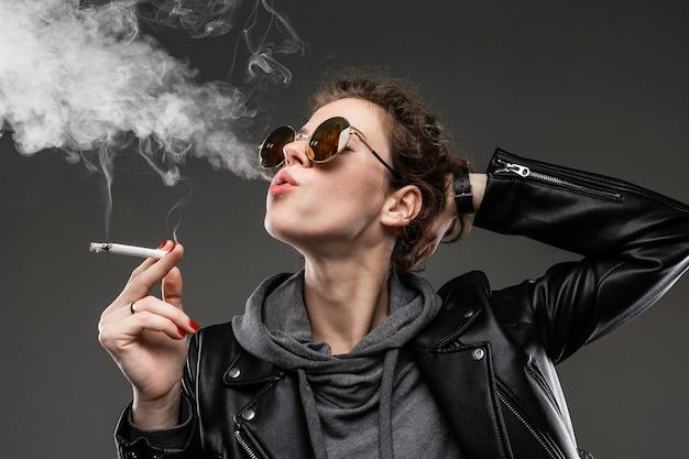 Junges mädchen mit rauen gesichtszügen in schwarzer jacke raucht isoliert Premium Fotos