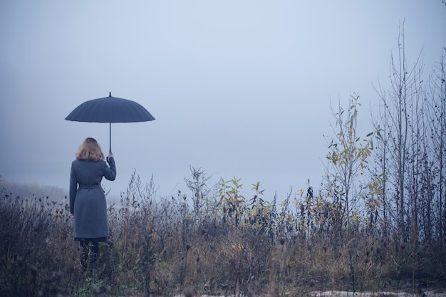 junges mädchen mit regenschirm im herbstfeld  premiumfoto