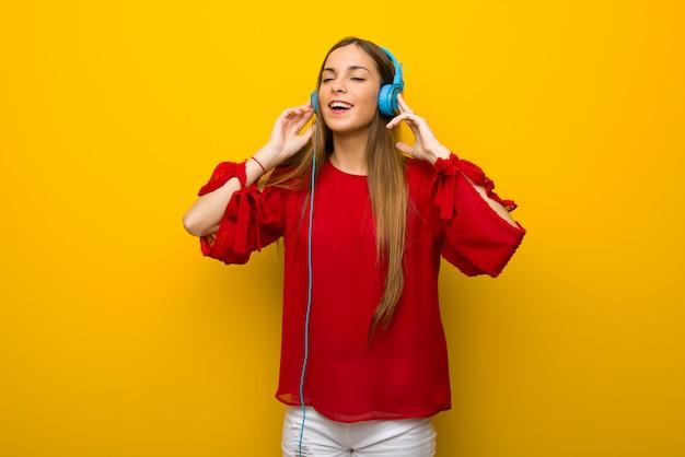 Junges mädchen mit rotem kleid über gelber wand hörend musik mit kopfhörern Premium Fotos