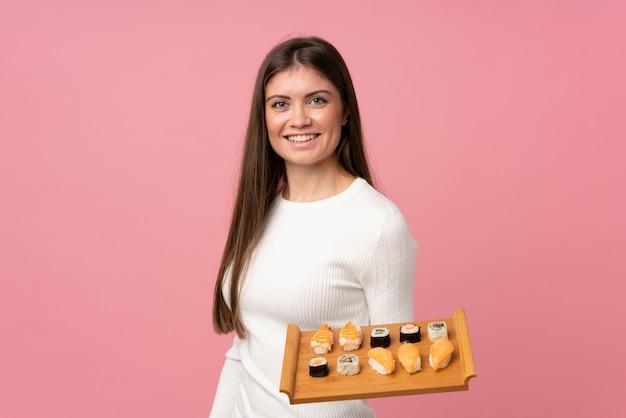 Junges mädchen mit sushi über lokalisiertem rosa hintergrund viel lächelnd Premium Fotos