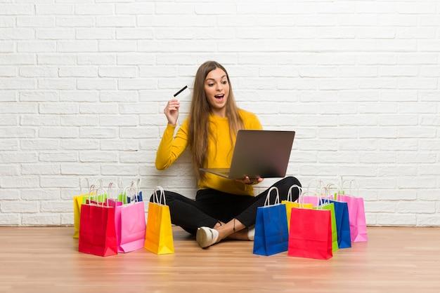 Junges mädchen mit vielen einkaufstüten mit laptop und kreditkarte Premium Fotos