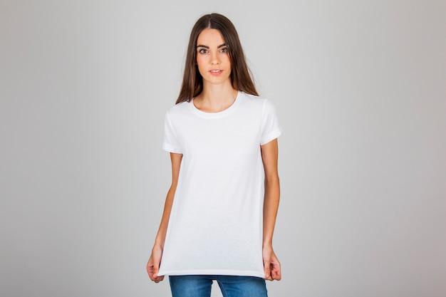 Junges mädchen posiert mit ihrem t-shirt Kostenlose Fotos