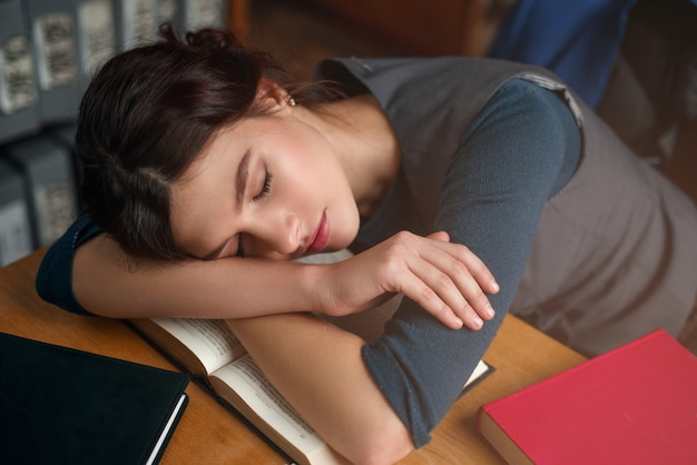 Junges mädchen schlief beim lesen eines buches ein. Premium Fotos