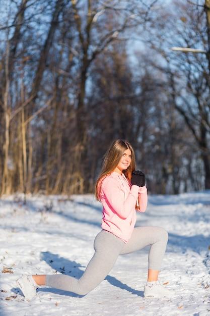 Junges mädchen strebt herein sport im winterpark an. Premium Fotos