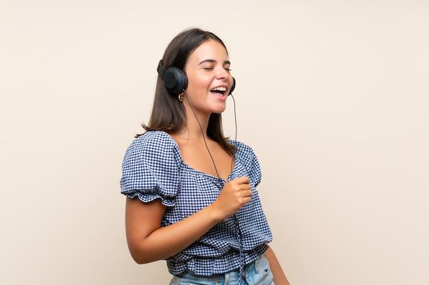 Junges mädchen über lokalisierter wand hörend musik mit kopfhörern Premium Fotos
