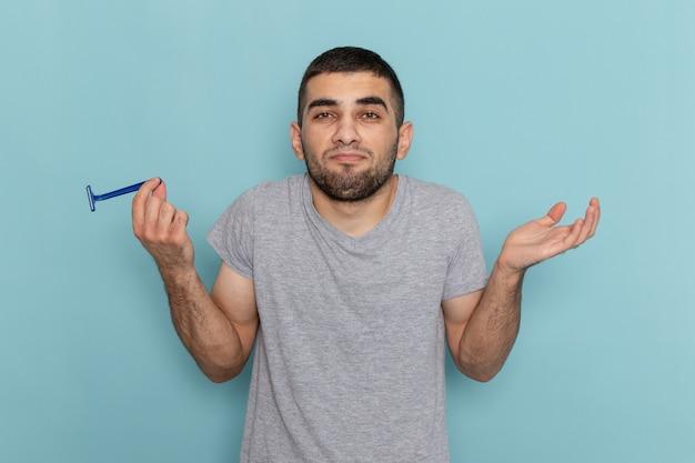 Junges männchen der vorderansicht im grauen t-shirt, das rasiermesser hält, das auf schaumfarbe des blauen rasierbart-männlichen haares aufwirft Kostenlose Fotos