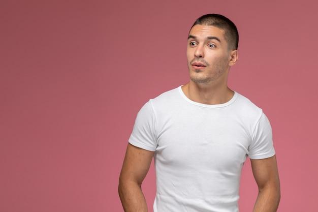 Junges männchen der vorderansicht im weißen t-shirt, das einfach auf dem rosa hintergrund aufwirft Kostenlose Fotos