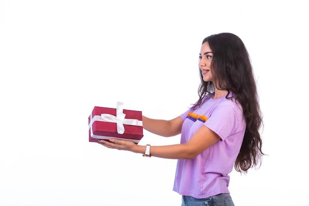 Junges modell, das eine rote geschenkbox, profilansicht hält Kostenlose Fotos