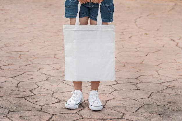 Junges modell, das weiße einkaufstasche für leere schablone des modells hält Premium Fotos