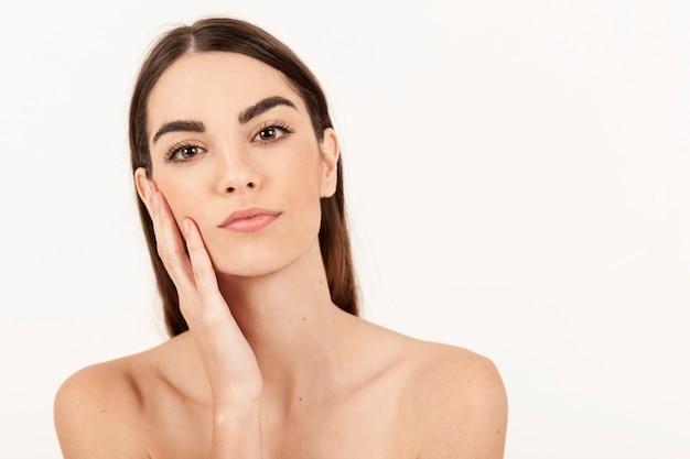 Junges modell posiert mit einer hand auf ihrem gesicht Kostenlose Fotos