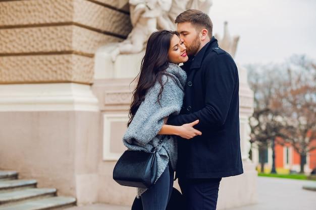 Junges modepaar, das auf der alten straße im sonnigen herbst aufwirft. hübsche schöne frau und ihr hübscher stilvoller freund, der auf der straße umarmt. Kostenlose Fotos