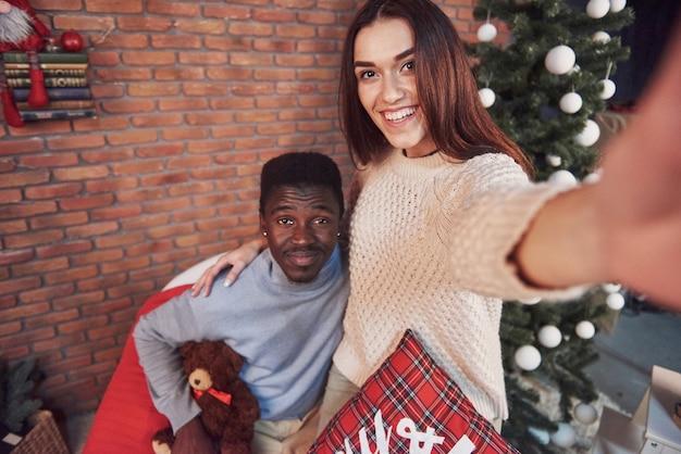 Junges multiethnisches paarsitzungsweihnachten, das nach hause umarmt. neujahr. feststimmung eines mannes und einer frau Premium Fotos