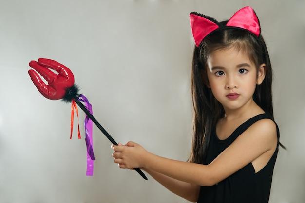 Junges nettes asiatisches mädchenkind, das im schwarzen teufelmode-kostüm ankleidet Premium Fotos