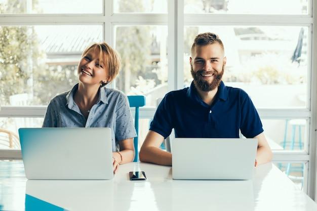 Junges paar arbeitet an laptops in einem café ein projekt zu tun, konferieren, freiberufler Kostenlose Fotos